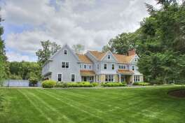 The custom-built colonial house at 2 Connors Lane in lower Weston sits in a very private setting of 2.33 level acres convenient to the centers of Weston and Westport.