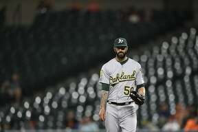 Oakland Athletics pitcher Mike Fiers pauses between pitches against the Baltimore Orioles in the third inning of a baseball game, Tuesday, Sept. 11, 2018, in Baltimore. The Athletics won 3-2.(AP Photo/Gail Burton)