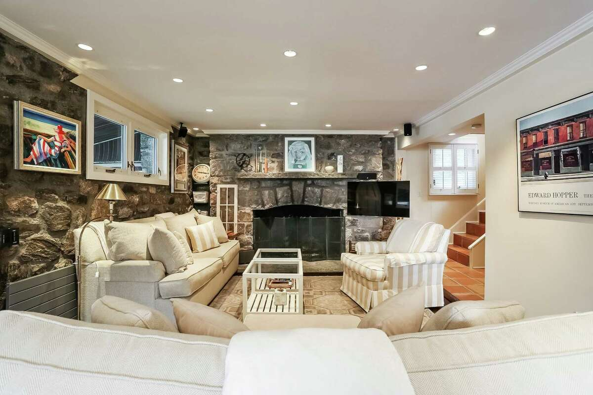 The large living room/dining room area includes an all stone, gas fireplace with stone mantel and a stone wall. Right: