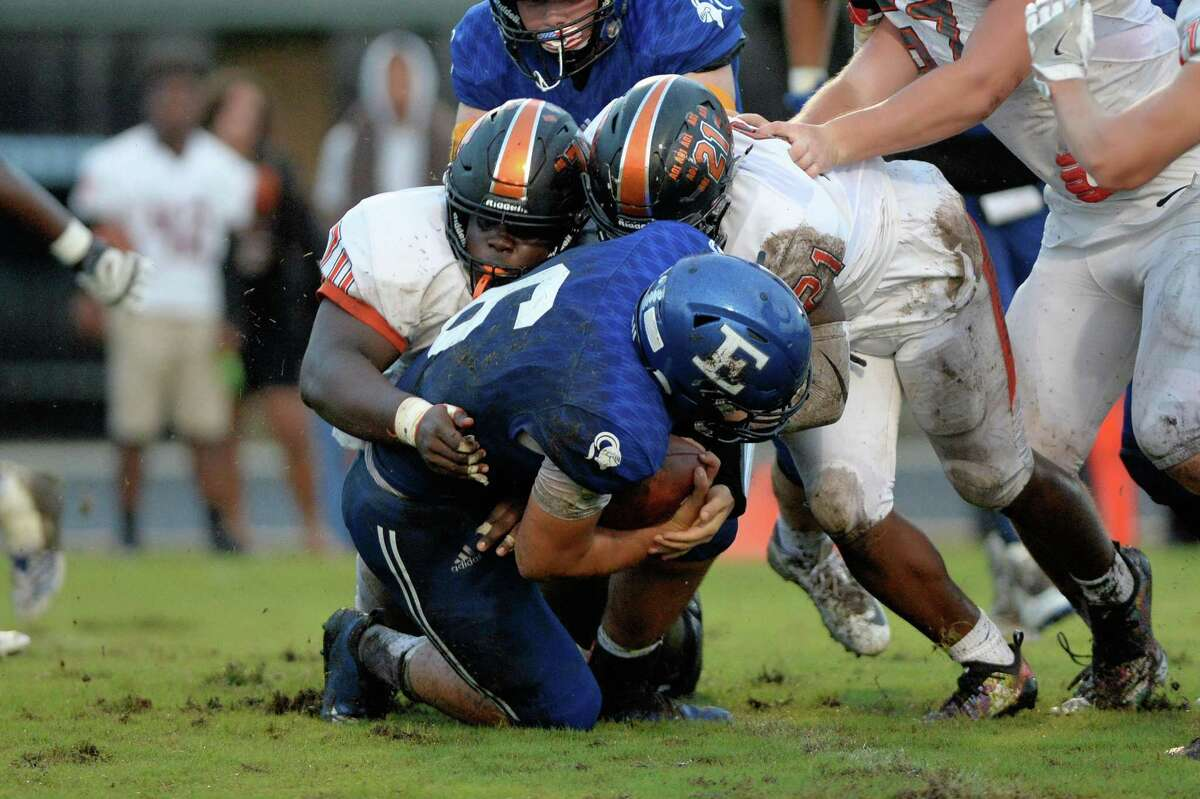 Nick Mayberry (6) of Episcopal carries the ball on a quarterback keeper but is tackled by Thomathan Good (70) and Ja'Kouvis Griffin (21) of St. Pius X in the first quarter of a high school football game between the Episcopal Knights and the St. Pius X Panthers on Friday, Sept. 14, 2018, at Episcopal High School in Bellaire.