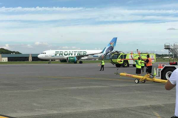 Frontier Airlines' first flight to Albany lands Monday morning at Albany International Airport. Airport fire trucks greeted the plane by spraying a traditional arc of water over the Airbus A321neo as it made its way to the gate.