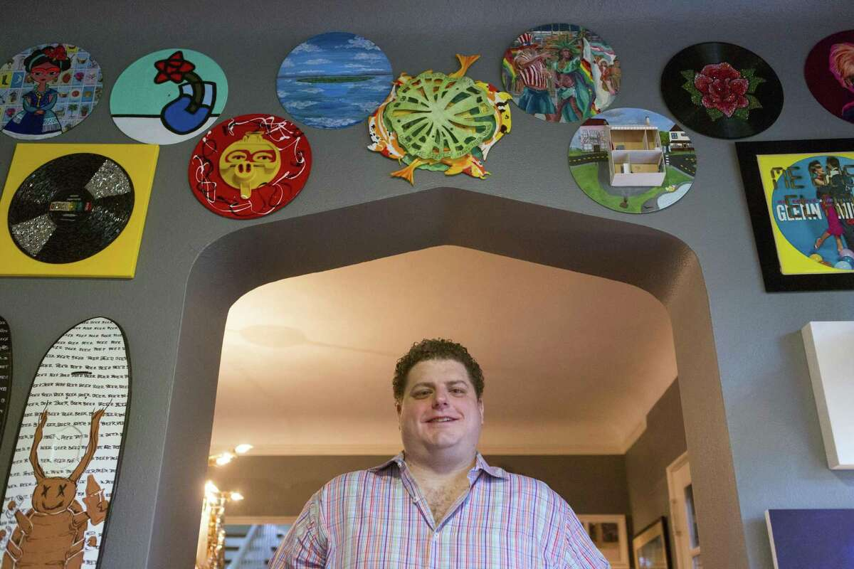 """Mike Wagner poses in his mother's home under some of the most recent pieces of art he and his mother purchased at the McNay Contemporary Collectors Forum event """"Art Vinyl: Spin It Your Way!"""""""
