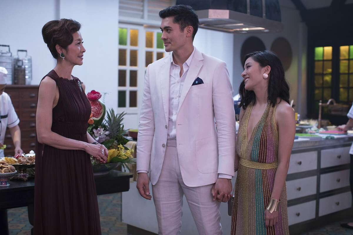 """This image released by Warner Bros. Entertainment shows Michelle Yeoh, from left, Henry Golding and Constance Wu in a scene from the film """"Crazy Rich Asians."""" When �Crazy Rich Asians� surpassed expectations and grabbed the top spot in its opening weekend, the film also pulled off another surprising feat. It put Asians of a certain age in theater seats. Younger Asian-Americans have been flocking with their parents to see the first movie in 25 years with an all-Asian cast. (Sanja Bucko/Warner Bros. Entertainment via AP)"""