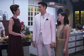 "This image released by Warner Bros. Entertainment shows Michelle Yeoh, from left, Henry Golding and Constance Wu in a scene from the film ""Crazy Rich Asians.""  When �Crazy Rich Asians� surpassed expectations and grabbed the top spot in its opening weekend, the film also pulled off another surprising feat. It put Asians of a certain age in theater seats. Younger Asian-Americans have been flocking with their parents to see the first movie in 25 years with an all-Asian cast. (Sanja Bucko/Warner Bros. Entertainment via AP)"