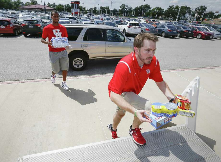 University of Houston Basketball player Justin Gorham (left)and UH's Director for Compliance Ted Seilheimer carry donations to a trailer for Hurricane Florence victim Monday, Sept. 17, 2018, in Houston. Houston Athletics and CEVA Logistics accepted donations for people who were significant impacted from Hurricane Florence. Photo: Steve Gonzales, Houston Chronicle / Staff Photographer / © 2018 Houston Chronicle