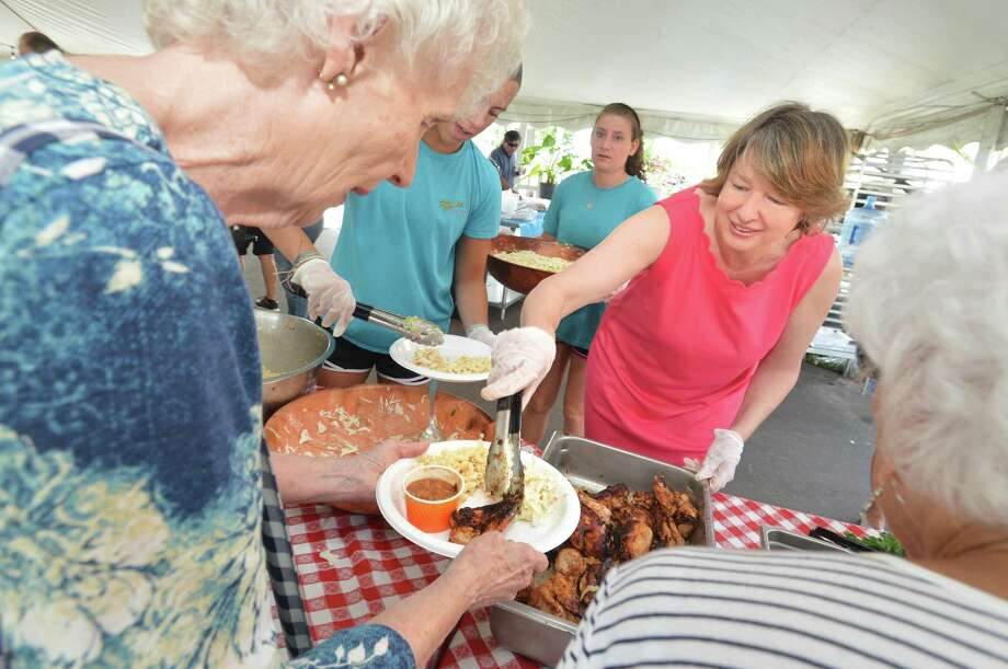 Beatrix Winter, Norwalk Senior Center executive director, helps to serve guests during the senior center's annual picnic at Ripka's Beach cafe at Calf Pasture Beach on Monday in Norwalk. Guests were treated to hamburgers and hot dogs plus seafood, chicken salads and desserts. Photo: Alex Von Kleydorff / Hearst Connecticut Media / Norwalk Hour