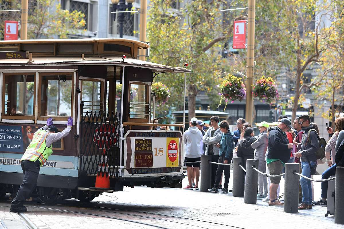 A cable car conductor helps turn a cable car next to people waiting in ine to board a cable car at Powell and Market Streets on Monday, September 17, 2018 in San Francisco, Calif.
