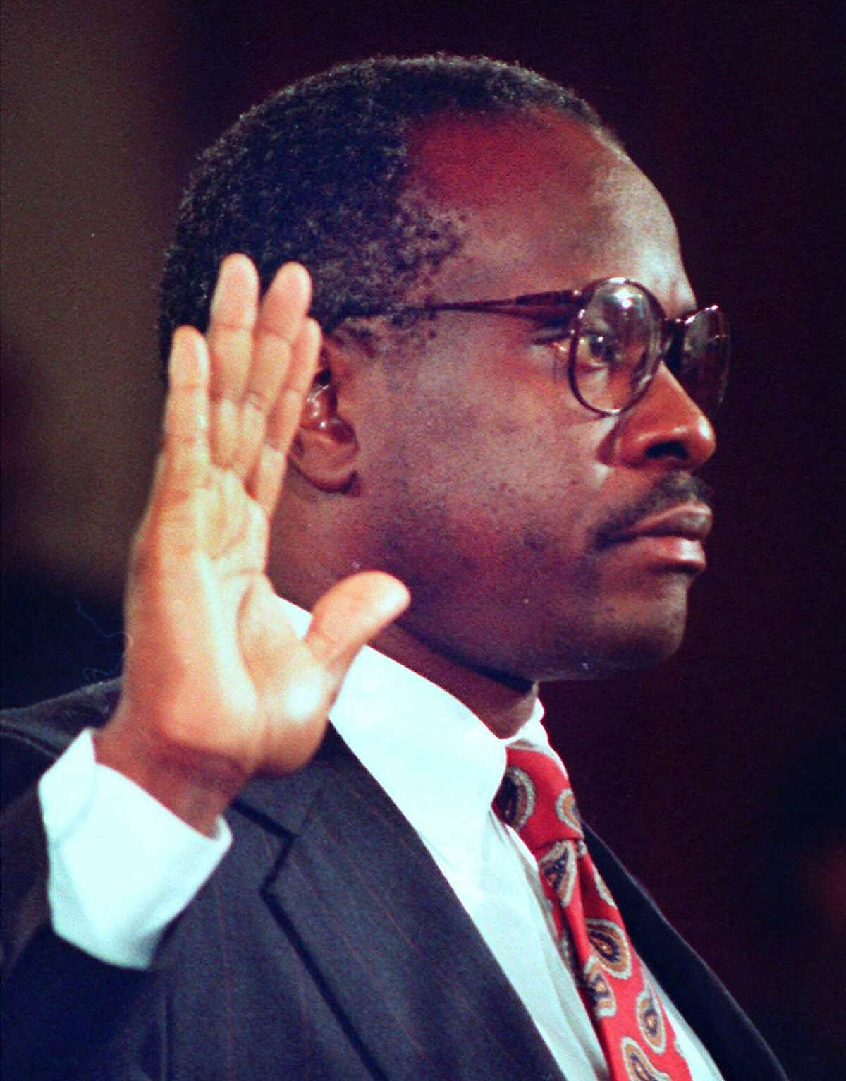 FILE--Judge Clarence Thomas is sworn in prior to testifying before the Senate Judiciary Committee on his nomination to the Supreme Court, on Capitol Hill in Washington, in this Oct. 11, 1991 file photo. After a decade on the nation's high court, Thomas, the second black to serve on the court, has settled into a comfortable routine. (AP Photo/Greg Gibson, File)