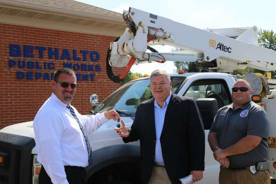 "Ameren Illinois Division Director Jason Klein, left, hands the keys to a 2009 Ford F-550 bucket truck to Bethalto Mayor Alan Winslow. Tim Brown, right, Bethalto Building and Zoning Administrator, requested the ""retired"" truck from Ameren Illinois. Photo: For The Telegraph"