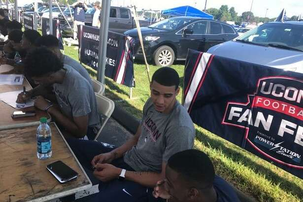 UConn senior Kwintin Williams chats with a teammate during an autograph session on Saturday at Rentschler Field.
