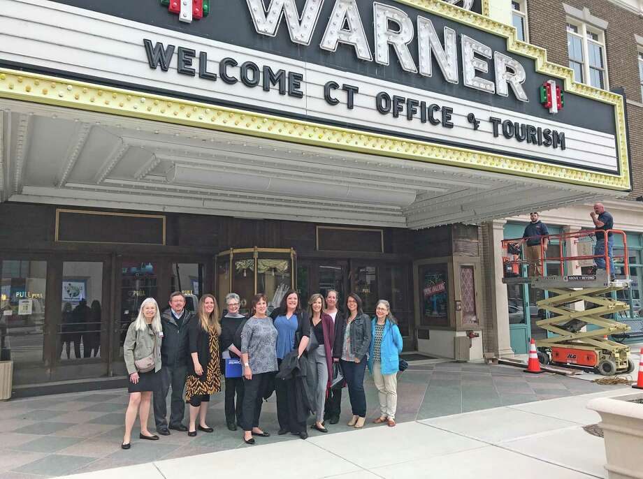 The Warner Theatre draws more than 100,00 people annually from Connecticut, 39 states and 2 countries. Read more in JoAnn Ryan's column below.  Pictured:Members of the Connecticut Office of Tourism with represntatives of the city's arts organization pose under the Warner Theatre marquee during a recent vist to the city. Photo: Jack Sheedy /