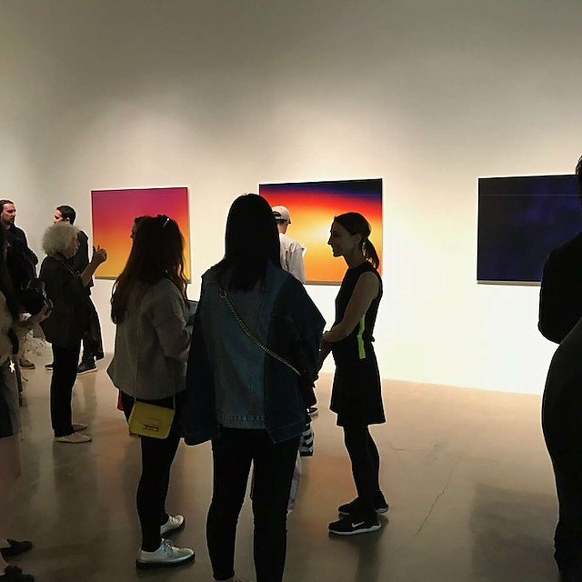 Visitors to SFAC Gallery's 10,000 Fahrenheit, silhouetted against images by Lisa Blatt