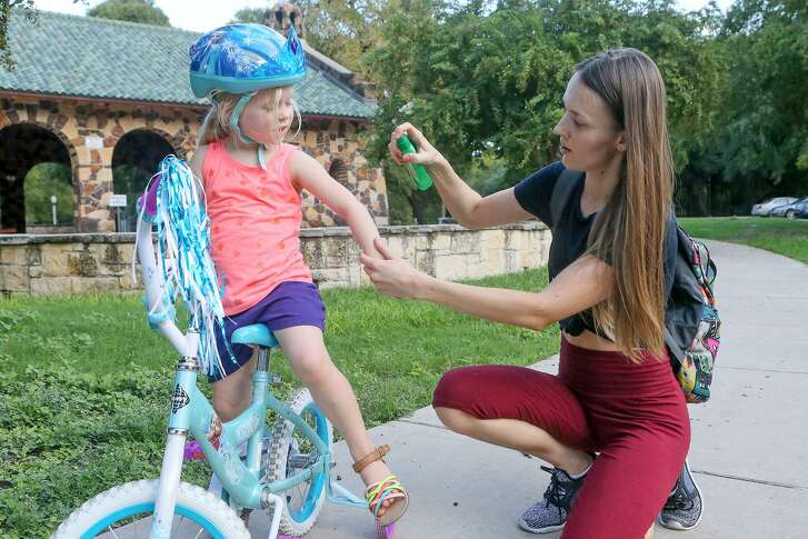 Agata Herrick sprays mosquito repellent on her daughter, Genesis Herrick, 3, before a bike ride in Brackenridge Park on Sept. 17, 2018. Health officials warned the public to watch out for mosquitoes that are breeding quickly because of the recent storms.