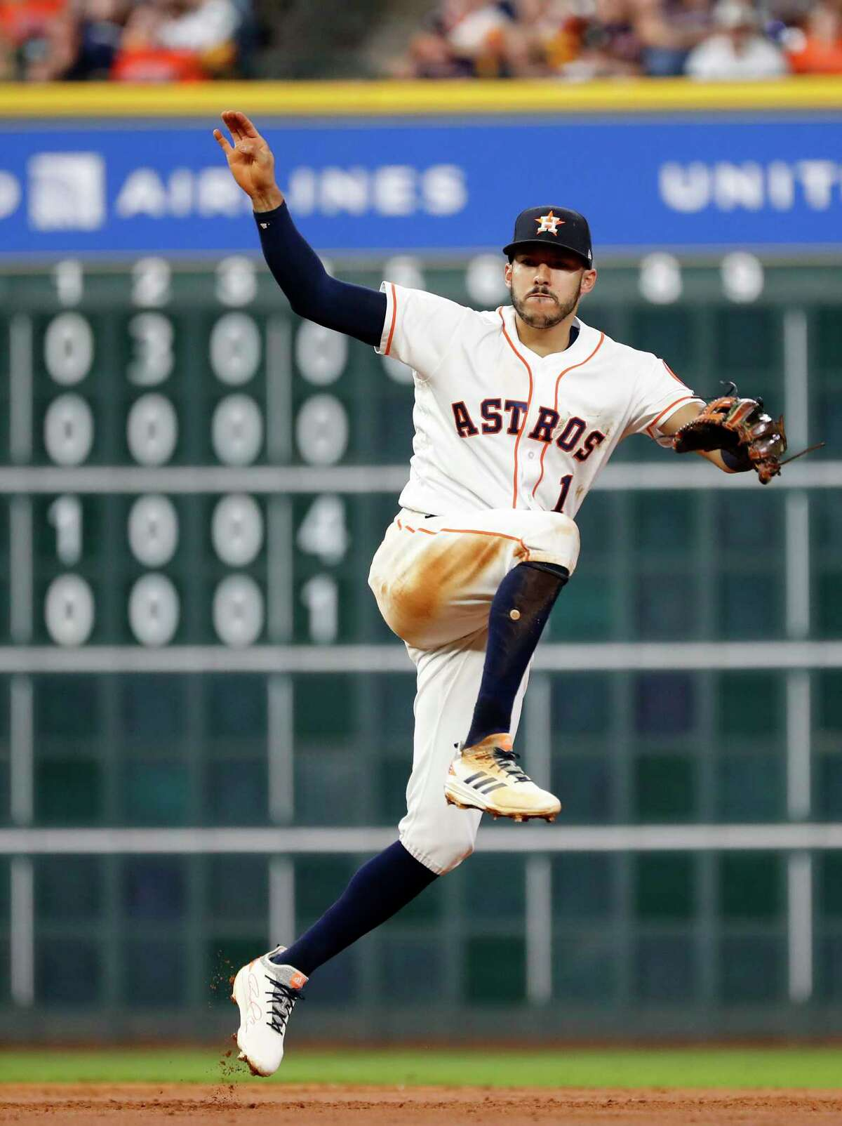 Houston Astros Carlos Correa (1) makes the throw to first as Seattle Mariners Nelson Cruz (23) ground into a double play during the third inning of an MLB game at Minute Maid Park, Monday, September 17, 2018, in Houston.