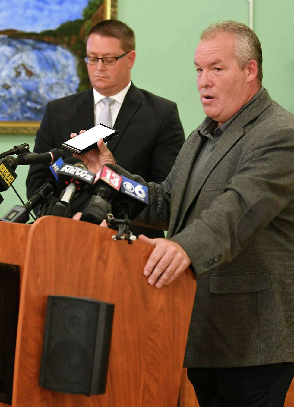 Cohoes Mayor Shawn Morse plays an audio of his upset wife from his cell phone as holds a press conference to speak out about the latest allegations and what's been going on with his family's life at Cohoes City Hall on Monday, Sept. 17, 2018 in Cohoes, N.Y. Morse said he doesn't plan on stepping down from his job. His attorney Joseph Ahearn listens at left. (Lori Van Buren/Times Union)