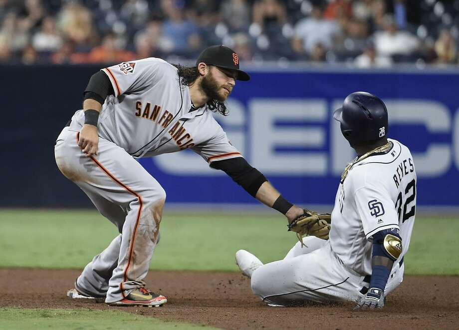 Brandon Crawford tags out Padres' Franmil Reyes in the sixth inning Monday night. Reyes tried to stretch a single to a double but was cut down by an Austin Slater throw from the right-field corner. Photo: Denis Poroy / Getty Images