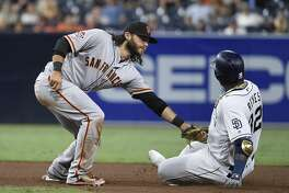 SAN DIEGO, CA - SEPTEMBER 17: Franmil Reyes #32 of the San Diego Padres is tagged out at second base by Brandon Crawford #35 of the San Francisco Giants as he tries to stretch a single during the sixth inning of a baseball game at PETCO Park on September 17, 2018 in San Diego, California. (Photo by Denis Poroy/Getty Images)