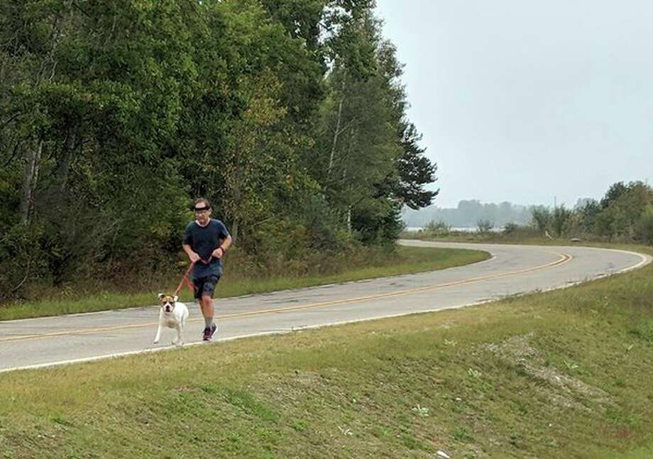Brian Andersen runs Friday with one of the adoptable dogs at the Gladwin County Animal Shelter. Andersen has been voluntarily running with the dogs for two years. (Tereasa Nims/For the Daily News)