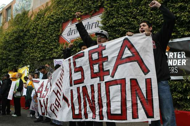 Brian Ponte (right) joins other fastfood employees blocking the drive-thru window at a McDonald's restaurant on East 12th Street in Oakland, Calif. on Thursday, Aug. 29, 2013. The action was part of a nationwide strike by workers demanding union representation and higher minimum wages.