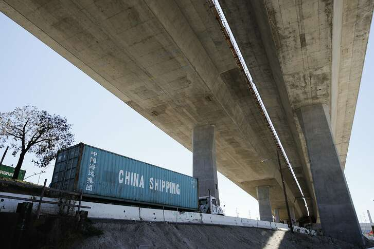 FILE- In this July 2, 2018, file photo, a truck carrying a cargo container drives under the Gerald Desmond Bridge under construction in Long Beach, Calif. China on Tuesday, Sept. 18, announced a tariff hike on $60 billion of U.S. products in response to President Donald Trump's latest duty increase in a dispute over Beijing's technology policy. (AP Photo/Jae C. Hong, File)