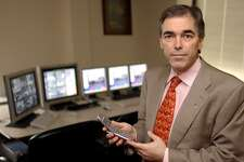 Jay Walker holds a cell phone at his offices in Stamford, Conn., on March 20, 2003. Walker is founder and executive chairman of Stamford-based Walker Innovations, a Stamford-based company focused on commercializing Walker's intellectual property. The firm has announced that it plans to dissolve on Sept. 20, 2018.