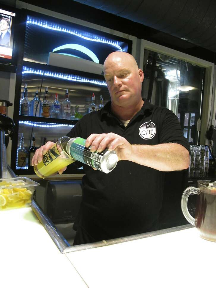 """Bartender Rodney Shipp pours a can of """"Alegae Bloom"""" beer at Maumee Bay Brewing Co. in Toledo, Ohio, on Wednesday, Sept. 12, 2018. The brewery is making the green, murky beer to draw attention to the algae blooms that taint Lake Erie's water. Craft brewery operators whose most important ingredient comes from the nation�s lakes and rivers are becoming a strong voice for clean water.   (AP Photo/John Seewer)"""