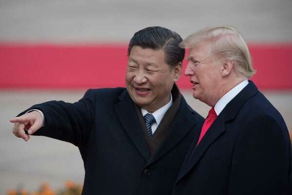"""(FILES) In this file photo taken on November 9, 2017 China's President Xi Jinping (L) and US President Donald Trump attend a welcome ceremony at the Great Hall of the People in Beijing. - President Donald Trump on September 18, 2018 accused China of seeking to influence upcoming US elections by taking aim at his political support base in the countries' escalating trade war. """"China has openly stated that they are actively trying to impact and change our election by attacking our farmers, ranchers and industrial workers because of their loyalty to me,"""" Trump tweeted.Trump's comments came a day after he targeted another $200 billion in Chinese imports with tariffs starting next week, drawing an immediate vow of retaliation from Beijing. (Photo by NICOLAS ASFOURI / AFP)NICOLAS ASFOURI/AFP/Getty Images"""