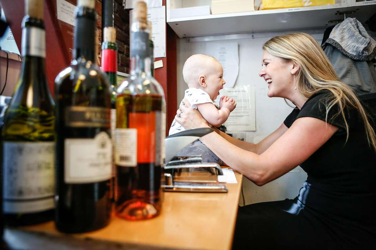 Haley Moore, beverage director at Salt House, Town Hall, and Anchor & Hope shares a moment with her 4 month old son, Miles, as she works in the office at Town Hall on Thursday, September 13, 2018 in San Francisco, Calif. Moore's employeers