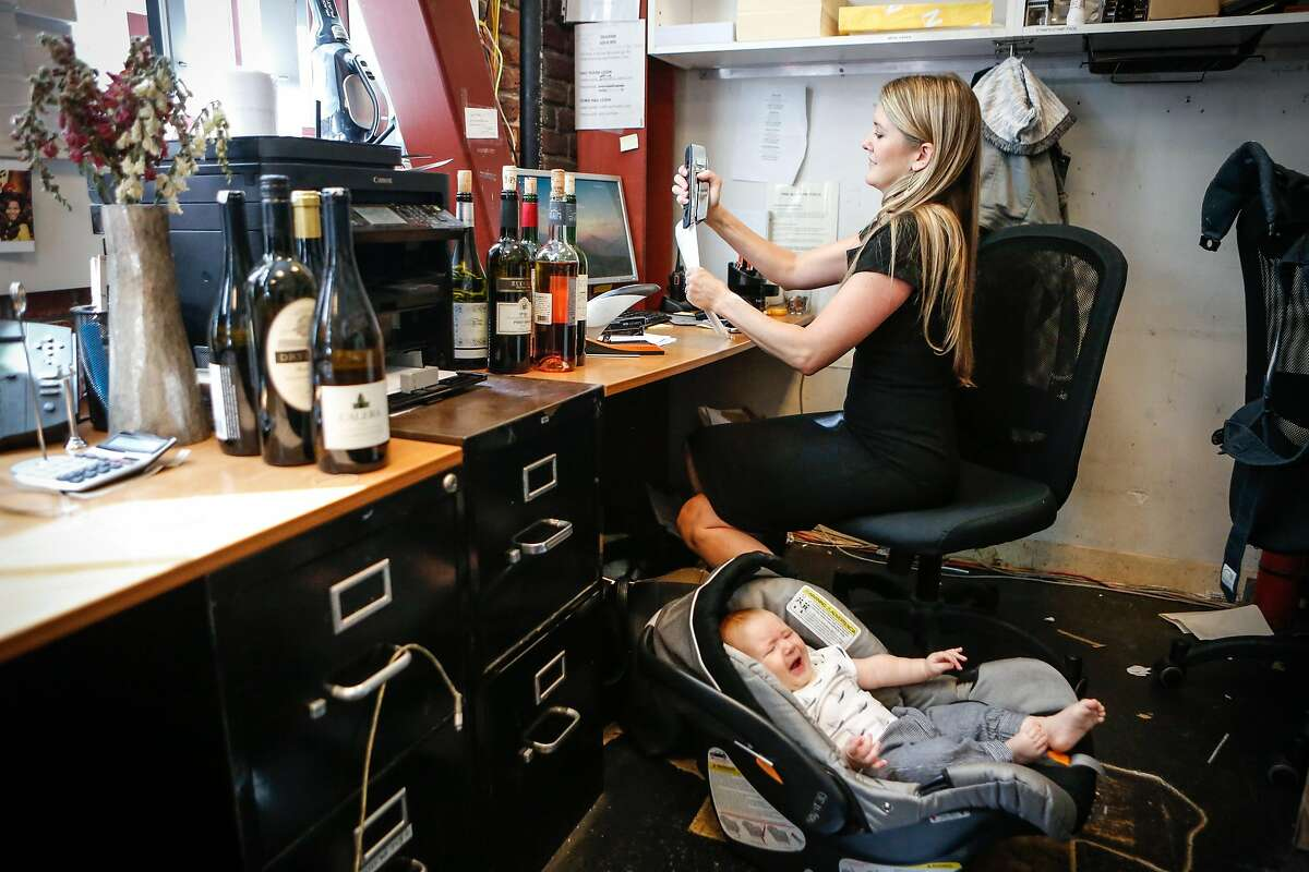 Haley Moore, beverage director at Salt House, Town Hall, and Anchor & Hope finishes stapling before she attends to her 4 month old son, Miles, as she works in the office at Town Hall on Thursday, September 13, 2018 in San Francisco, Calif. Moore's employeers