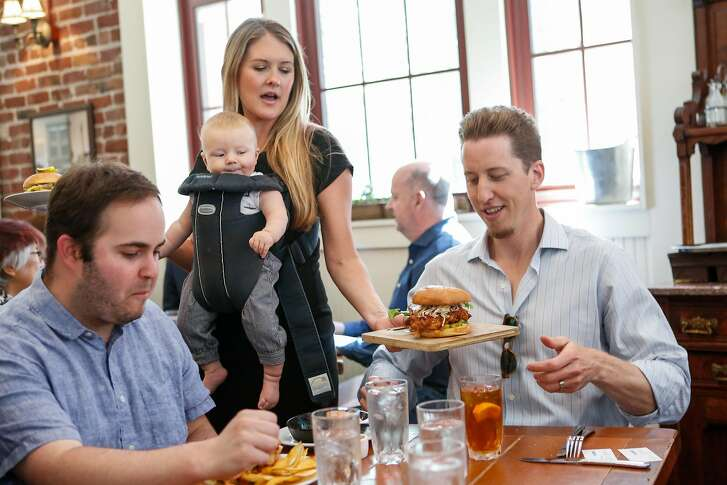 Haley Moore, beverage director at Salt House, Town Hall, and Anchor & Hope wears her 4 month old son, Miles, in a carrier while helping deliver food to a table (who did not wish to be identified) during the lunch rush at Town Hall on Thursday, September 13, 2018 in San Francisco, Calif.