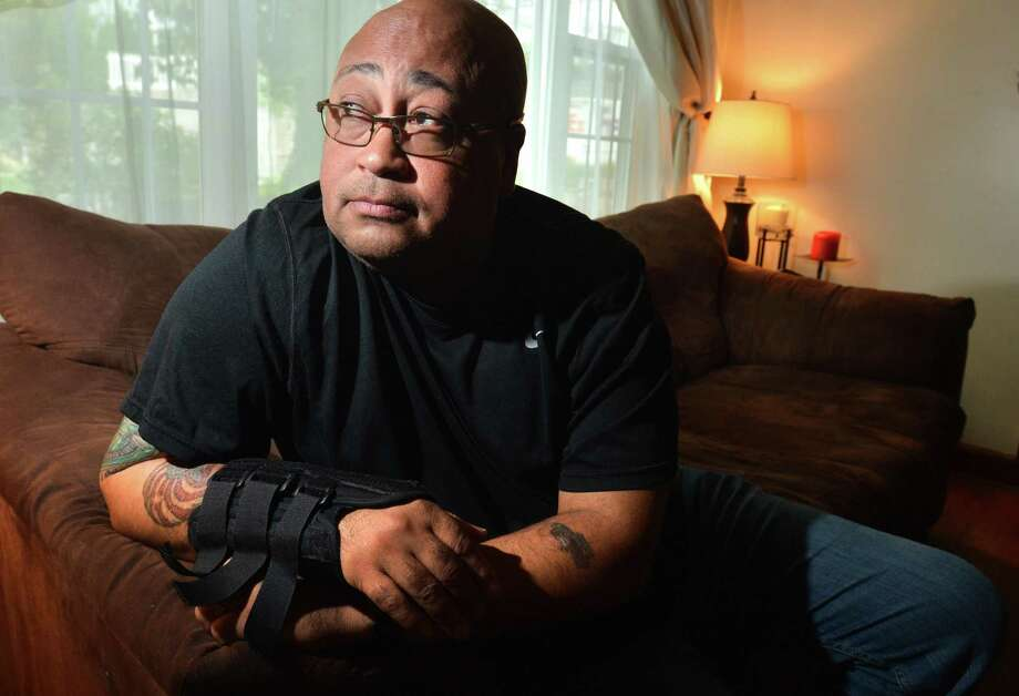 Patrolman Phil Roselle, at his Norwalk Conn. home on Monday September 17, 2018, Roselle, a 30-year veteran of the Norwalk Police Department, has been off the job for a year after an accidental discharge by another at the police shooting range left him with a bullet lodged in his rib and nerve damage to his right arm, and many other health issues and costs as his work benefits from the city have ended. Photo: Alex Von Kleydorff / Hearst Connecticut Media / Norwalk Hour