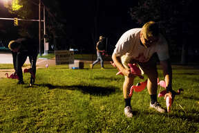 """From left, Midland residents Jake Trumpie, 23, Zack Howell, 18, and Jared McNitt, 22, place plastic flamingoes in the front lawn at the home Howell lives in with his parents as part of the annual """"flocking"""" fundraiser for Midland Young Life on Thursday, Sept. 13, 2018. For the month of September, participants can make a donation to the church and nominate a friend or relative to be """"flocked."""" For more photos, go to www.ourmidland.com. (Katy Kildee/kkildee@mdn.net)"""