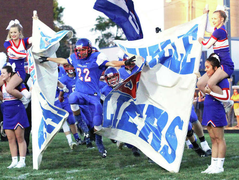 Carlinville sophomore Lonny Rosentreter (22) breaks through the banner as the Cavaliers take the field before Friday night's SCC game with Carlinville. The Cavs won 49-12 to improve to 4-0. Pana is 3-1. Photo: Greg Shashack | The Telegraph