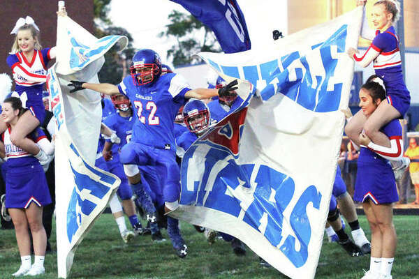 Carlinville sophomore Lonny Rosentreter (22) breaks through the banner as the Cavaliers take the field before Friday night's SCC game with Carlinville. The Cavs won 49-12 to improve to 4-0. Pana is 3-1.