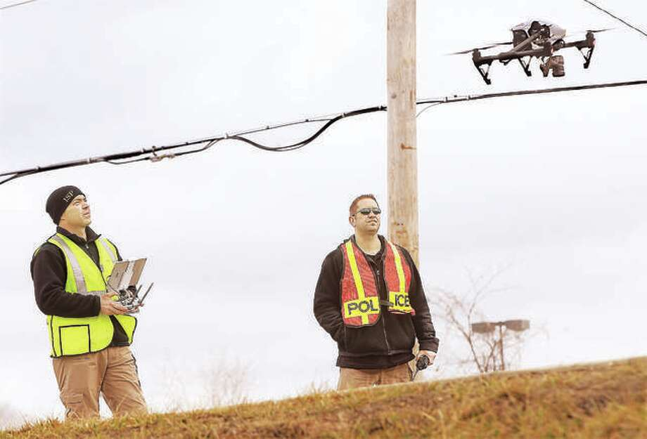 In this photo from February, two Illinois State Police troopers, one operating the controls, left, watch as their drone lifts off from Buckmaster Lane just to the north of the Homer Adams Parkway in Alton to begin a series of photographs as part of a reconstruction effort into a fatal two-vehicle crash. With help from a grant, the Alton police and fire departments will soon have a drone of their own to assist in investigations and rescues. Photo: John Badman | The Telegraph