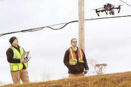 In this photo from February, two Illinois State Police troopers, one operating the controls, left, watch as their drone lifts off from Buckmaster Lane just to the north of the Homer Adams Parkway in Alton to begin a series of photographs as part of a reconstruction effort into a fatal two-vehicle crash. With help from a grant, the Alton police and fire departments will soon have a drone of their own to assist in investigations and rescues.