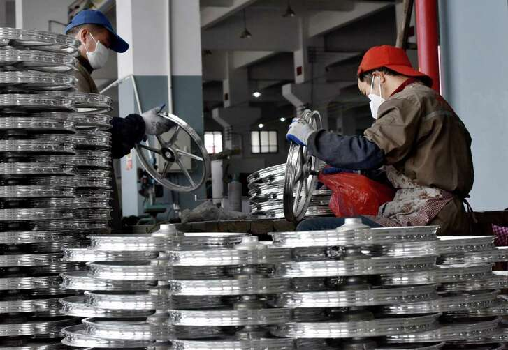 Chinese laborers work on bicycle parts. Trade tension with Beijing is adding additional risk to the U.S. economy.
