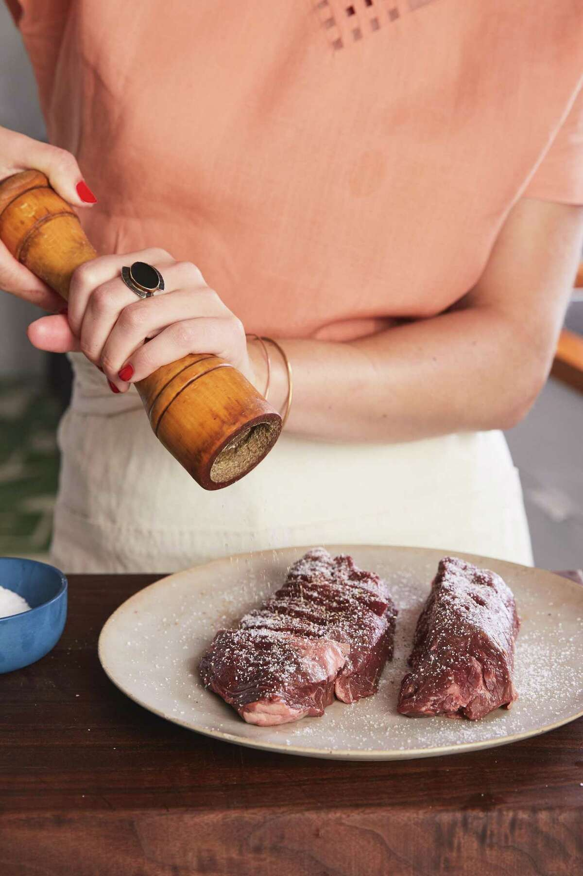 Steak is seasoned with salt and pepper, part of the preparation for butcher?'s steak with leafy greens salsa verde, in New York, July 17, 2018. An affordable cut doesn't mean you have to skip out on flavor, just ask New York Times columnist Alison Roman ?- who asks her butcher. (Michael Graydon & Nikole Herriott/The New York Times)