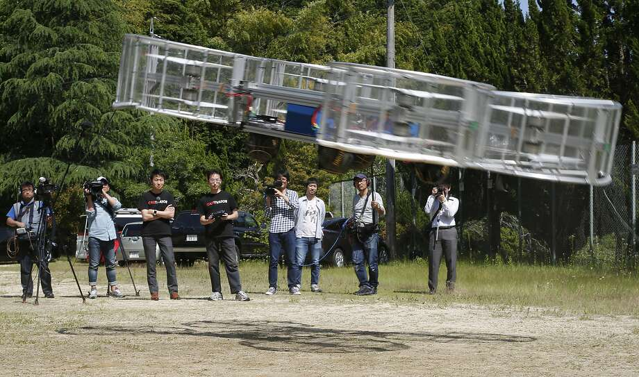 Tsubasa Nakamura (third from left), project leader of Cartivator, watches a 2017 test flight of its flying car. Photo: Koji Ueda / Associated Press 2017