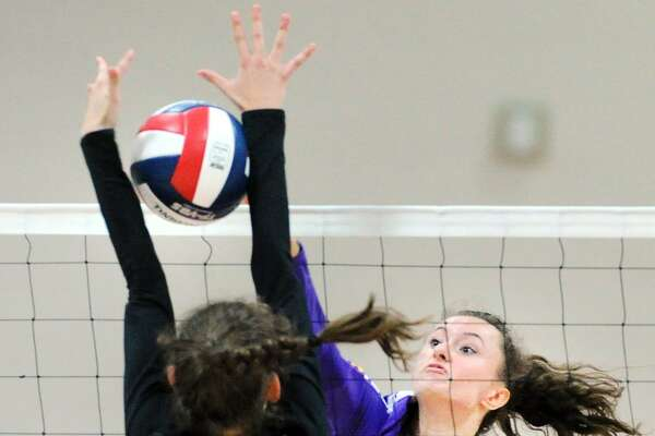 Westhill's Betsy Sachs of Westhill (13) drives a spike past New Canaan's Alexandra Gillespie during Tuesday's contest.