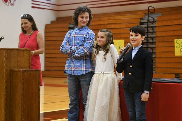 'Young Sheldon' cast member Iain Armitage (Sheldon), from right, with fellow cast members Raegan Revord (Missy), and Montana Jordan (Georgie), and Trisha Cardoso, President and Chief Giving Officer for the Chuck Lorre Family Foundation, speaks at midcourt in the Tomball High School gym during the assembly celebrating the presentation of the Young Sheldon STEM Initiative Grant that the Chuck Lorre Family Foundation awarded to five Tomball ISD schools on Sept. 17, 2018.