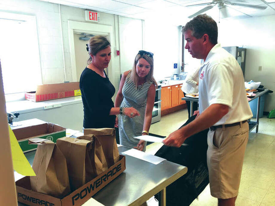 Madison County Board members Ann Gorman, left of Edwardsville, and Erica Conway-Harriss, center of Glen Carbon, help Edwardsville Mayor Hal Patton load meals for delivery on Tuesday as part of the Big Wheels Week program being conducted at the Main Street Community Center. Local leaders are volunteering their time to take part in the MSCC's Meals on Wheels program, delivering lunches to area seniors and disabled adults. Photo: Bill Tucker/Intelligencer