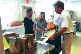 Madison County Board members Ann Gorman, left of Edwardsville, and Erica Conway-Harriss, center of Glen Carbon, help Edwardsville Mayor Hal Patton load meals for delivery on Tuesday as part of the Big Wheels Week program being conducted at the Main Street Community Center. Local leaders are volunteering their time to take part in the MSCC's Meals on Wheels program, delivering lunches to area seniors and disabled adults.