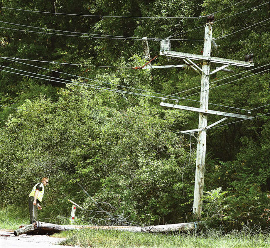 An Alton police officer looks at the severed but still hanging upper portion of a power pole that was broken Tuesday on Fosterburg Road near the entrance to Bottoms Up Sports Bar and Grill by the front of a semi-truck from Maw Salvage in Brighton. Alton firefighters were called to the scene to extinguish a small fire started by a downed power line when the pole broke. It was unclear how the accident happened, but the truck stopped about one-quarter of a mile down the road, dragging guide wires and power lines underneath it. No injuries were reported. Photo: John Badman | The Telegraph