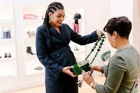 Owner Sherri McMullen, left, helps customer Jacqueline Boggan with a Cult Gaia acrylic purse by Luna, at her women's fashion shop McMullen at it's new location in Oakland, CA, on Monday September 17, 2018.