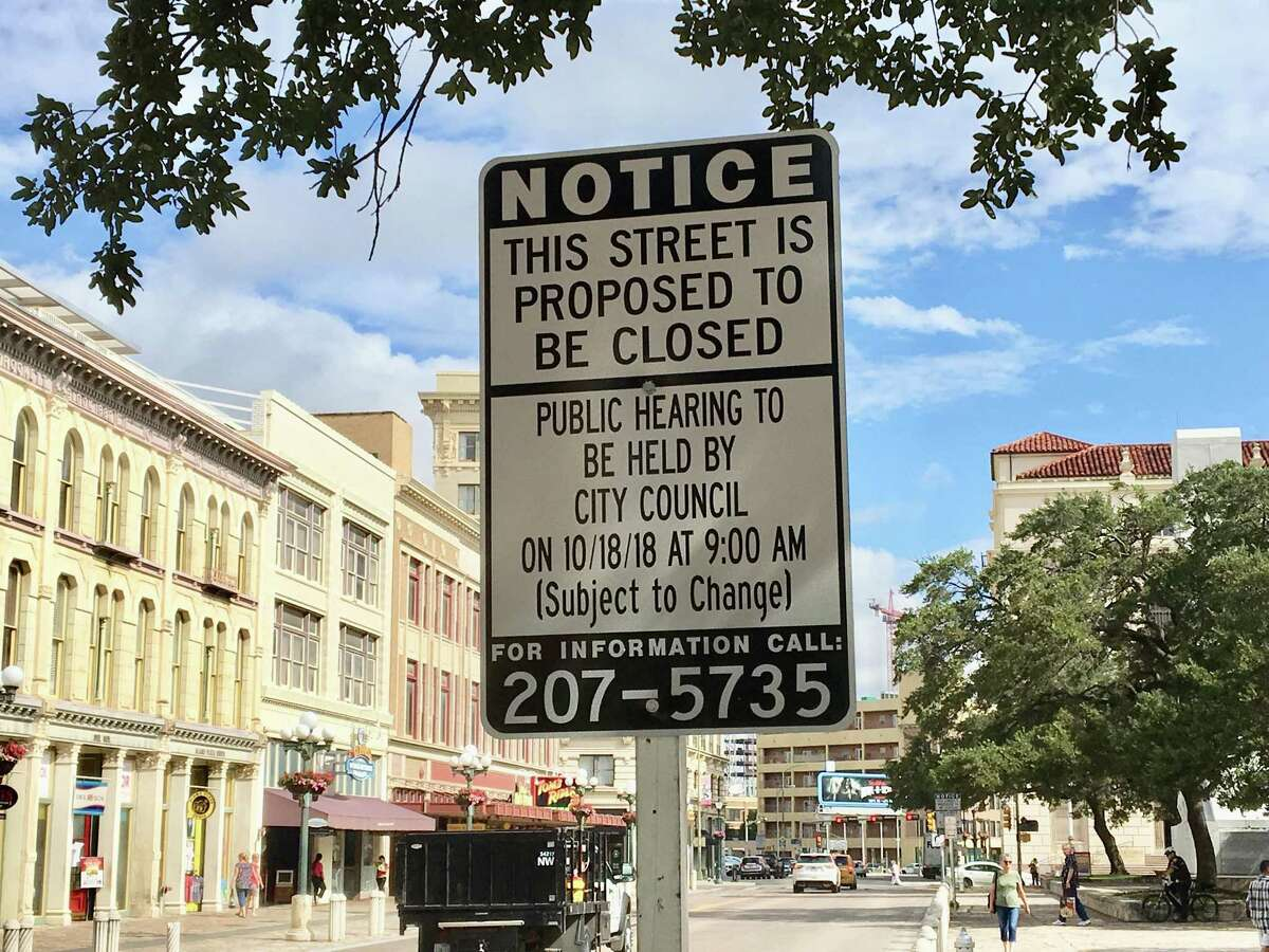 A sign posted on Alamo Street notifies the public of the upcoming hearing about the closure of the street to traffic.