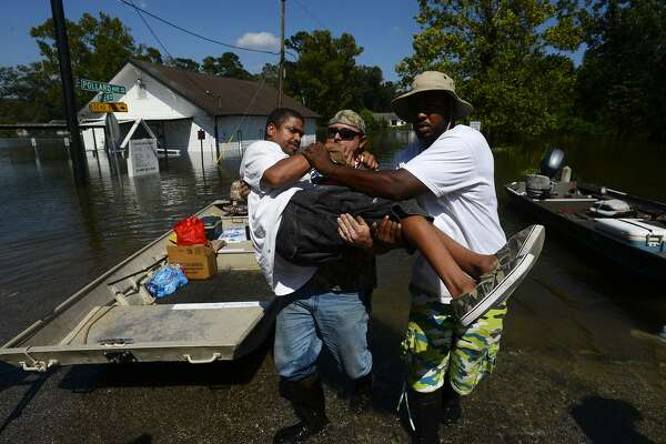 Chris McCarty and Mike Taylor help carry Quintin Sanders, who has cerebral palsy, off a rescue boat in the north end of Beaumont, Texas on Thursday, Aug. 31, 2017. McCarty came from Lufkin, Texas to help rescue people from flooding due to Tropical Storm Harvey. Photo taken Thursday 8/31/17 Ryan Pelham/The Enterprise