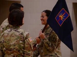 New York Army National Guard Maj. Amy Crounse receives guidon of the Joint Force Headquarters and Headquarters Detachment from Chief of Staff Col. John Andonie during a change of command in Latham.