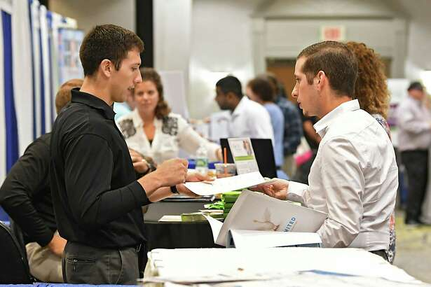 Michael DeCarr of CPS Recruitment, left, receives a resume from job seeker Anthony Schenkman of Troy during the Times Union Job Fair for manufacturing and technology openings in and around the Capital Region at the Albany Marriott hotel on Tuesday, Sept. 18, 2018 in Colonie, N.Y. (Lori Van Buren/Times Union)
