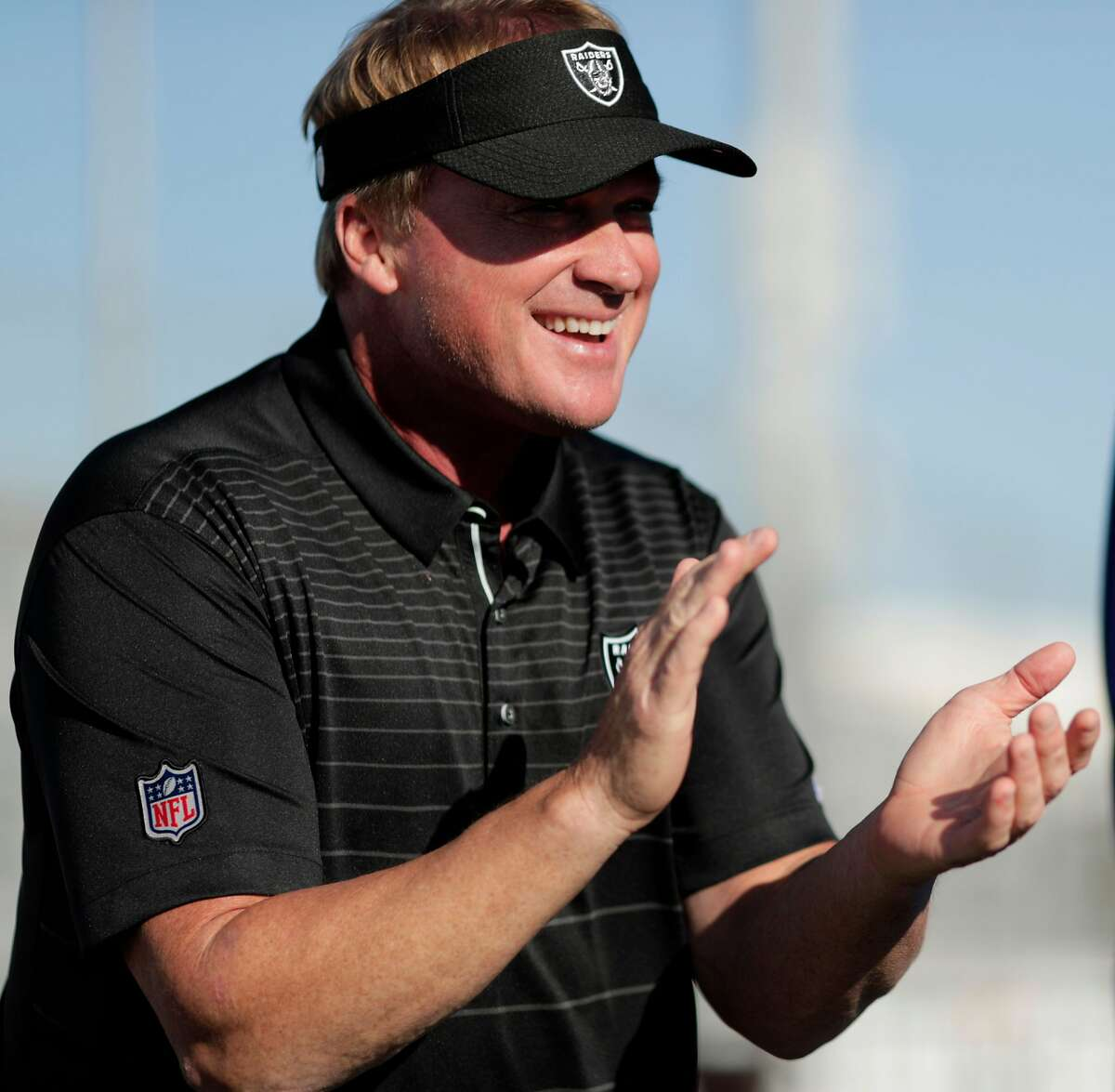 Oakland Raiders head coach Jon Gruden claps as kids pick up equipment and encouragement he delivered to about 60 kids from the San Leandro Crusaders and the East Bay Panthers at Burrell Field in San Leandro, Calif., on Tuesday, July 17, 2018. The gear, and $50000 was a joint donation of the Dick's Sporting Goods Foundation and Coach Gruden.